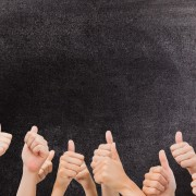digital composite of multiple thumbs up on chalkboard background